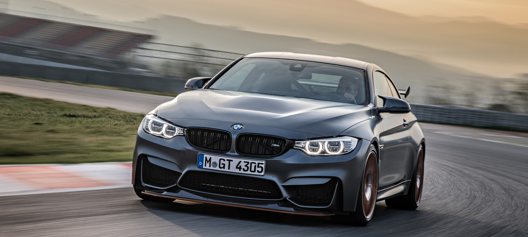 Driving BMW M4 GTS on racetrack with mountain range in the background