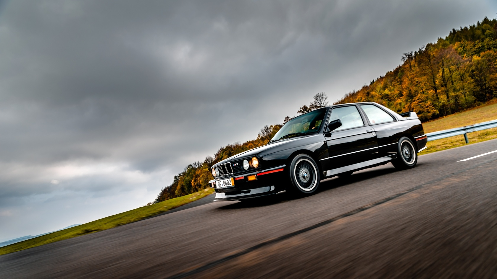 E30 BMW M3 Sport Evolution of Matthias Unger in paint finish Gloss Black driving on a road in autumn