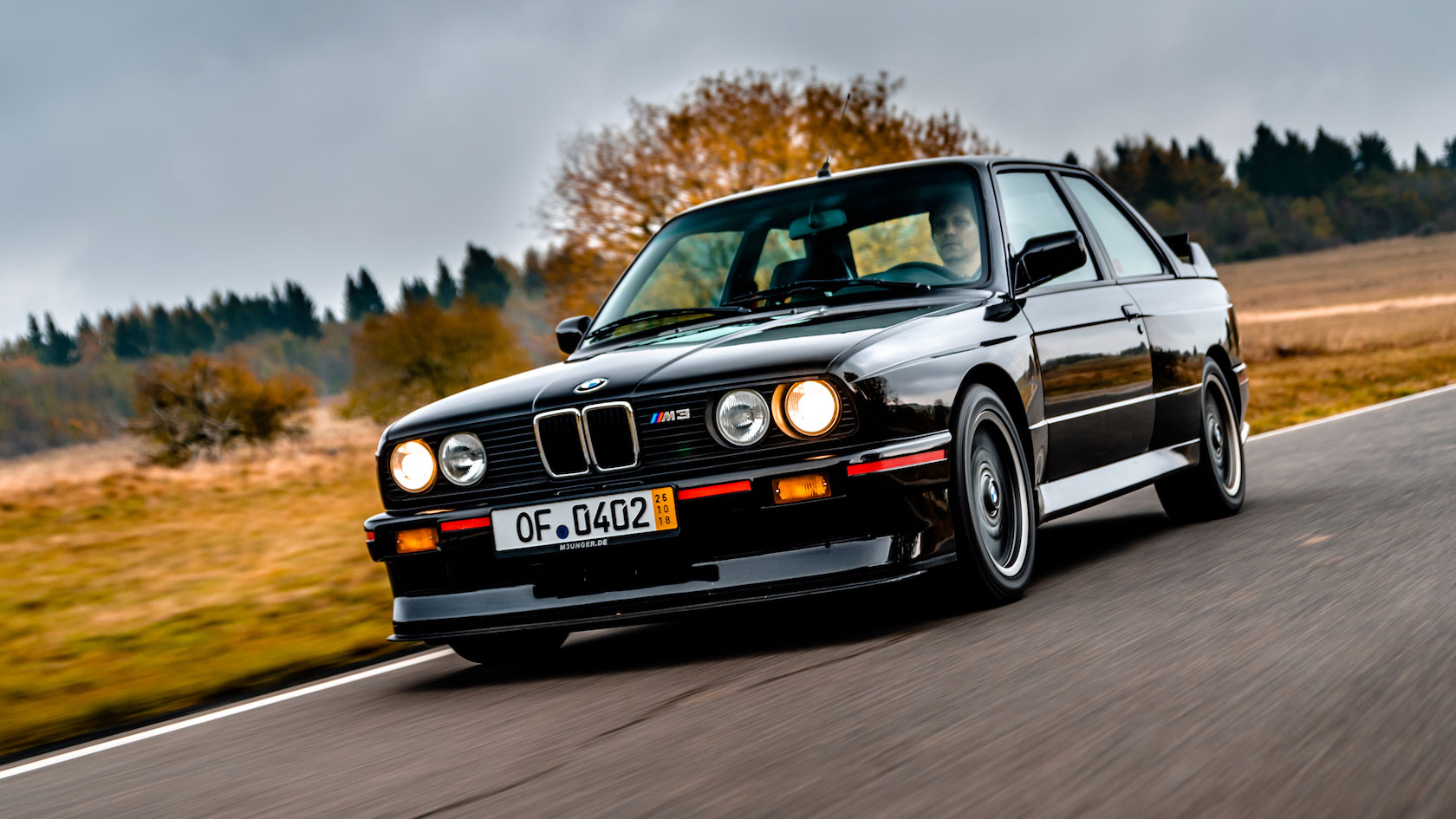 E30 BMW M3 Sport Evolution with paint finish Gloss Black on a counry road in autumn