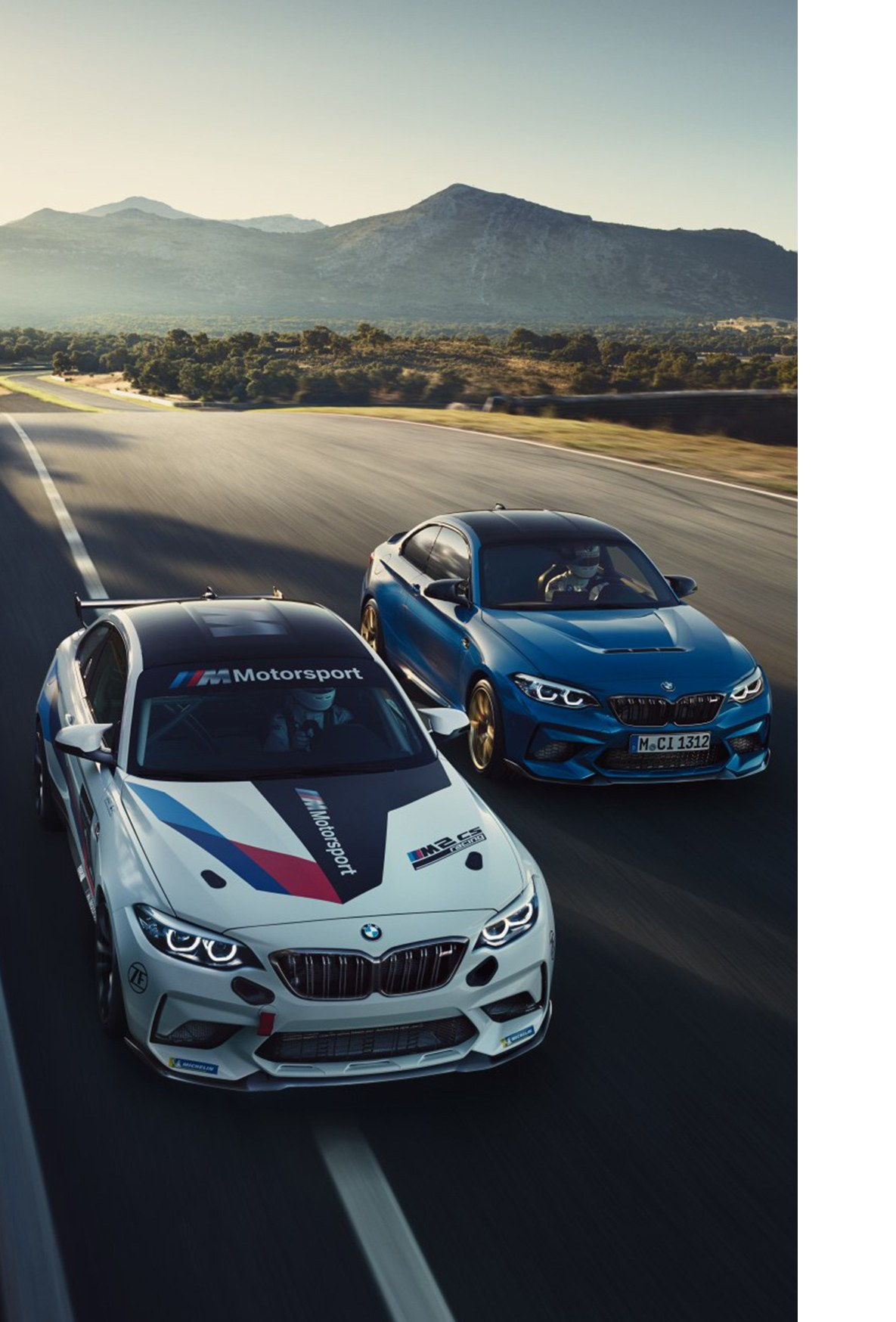 A BMW M2 CS Racing and a blue M2 CS driving together on a race track